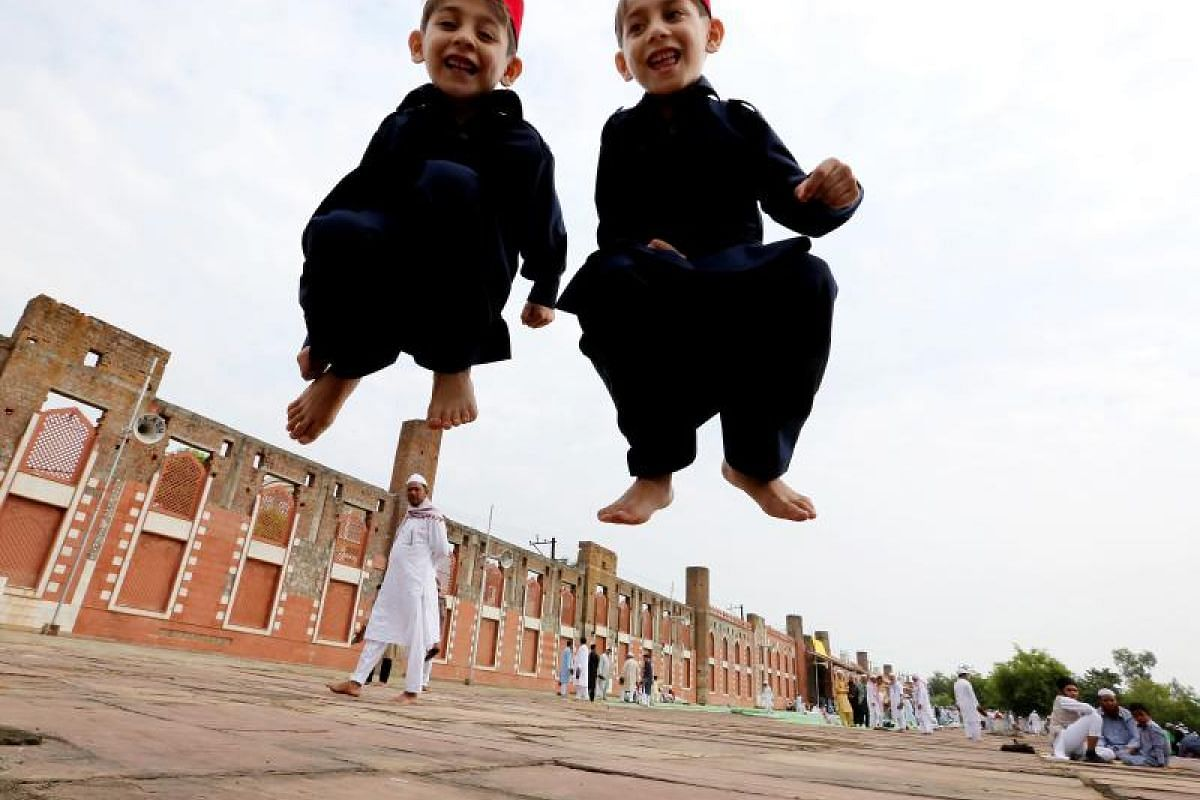 Two boys jumping for joy in anticipation of the celebrations ahead of them, after finishing their Eid al-Fitr prayers at the iconic Eidgah mosque in Bhopal, India on Monday (26 June).