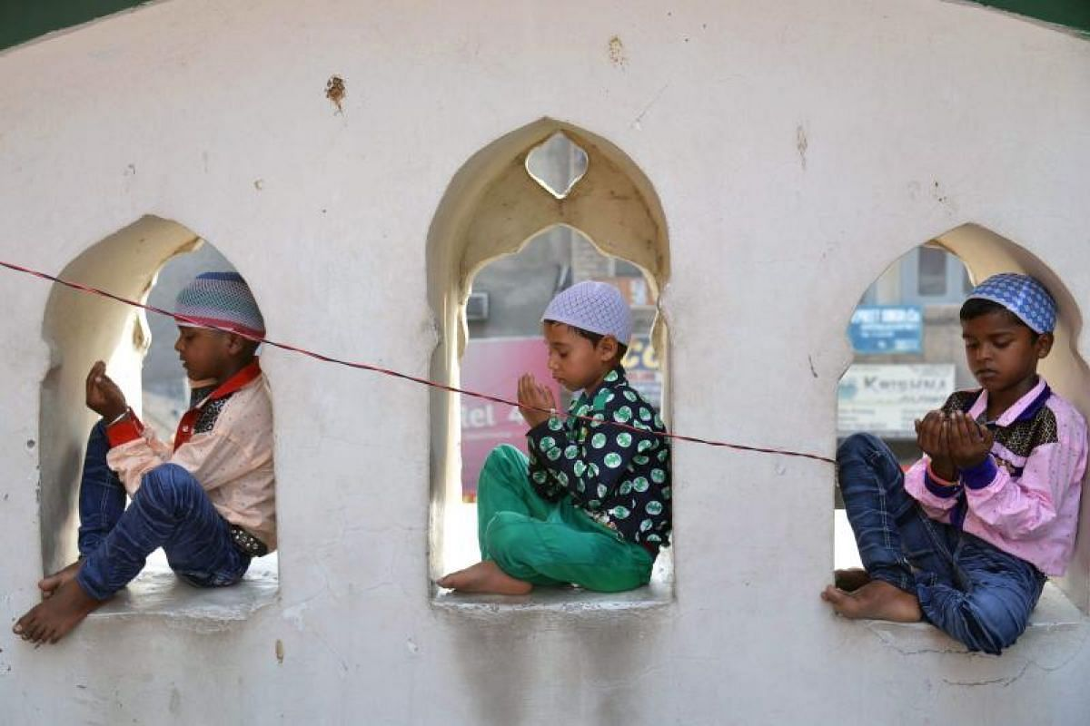 Three boys find their own little nook from which to do their Eid al-Fitr prayers at the Khairuddin Mosque in Amritsar on Monday (June 26).