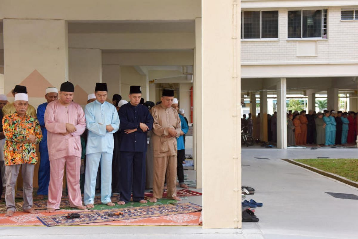Muslim residents in East Coast GRC coming together on the morning of Hari Raya Aidilfitri on Sunday (June 25) to do their prayers at the void deck of Block 108, Simei Street 1.