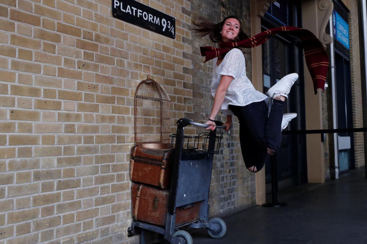 """The celebrations have rolled into town as this fan poses for a photograph with the Harry Potter trolley at Platform 9-3/4 at King's Cross Station in London. The """"platform"""" is the departure point for trains to Hogwarts School of Witchcraft and Wizardr"""
