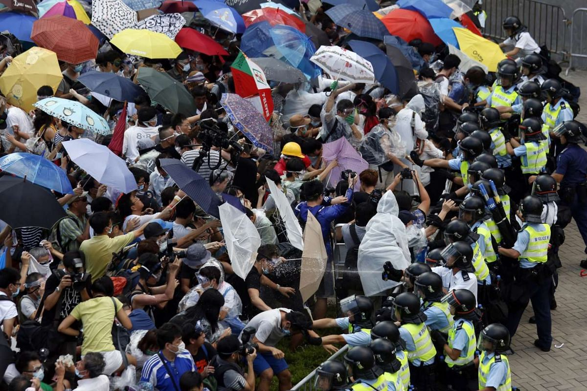 Pro-democracy protesters clashing with police during a massive blockade in central Hong Kong on Sept 28, 2014. The China and Hong Kong flags flutter from a tree in Hong Kong ahead of the 20th anniversary of the territory's handover to Chinese rule.