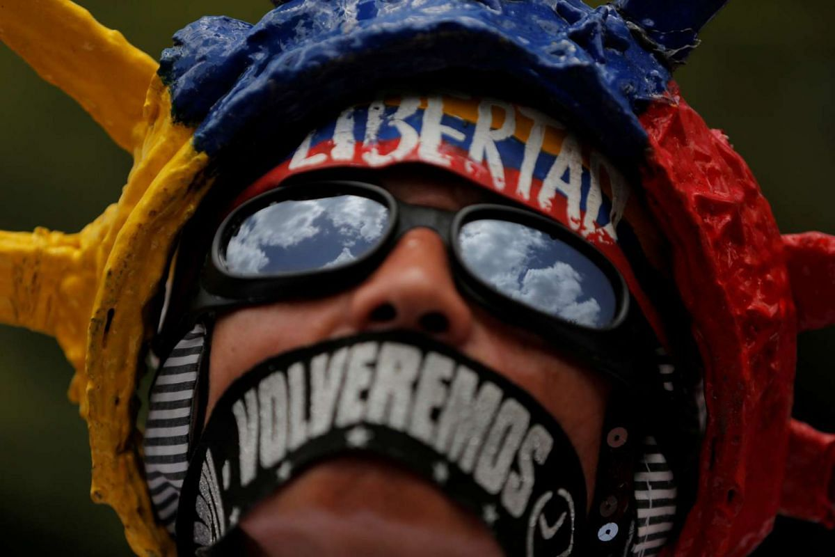 """A demonstrator displays writing on this face that reads, """"Freedom, we will return"""", as he attends a rally against Venezuela's President Nicolas Maduro's government in Caracas, Venezuela June 27, 2017. PHOTO: REUTERS"""