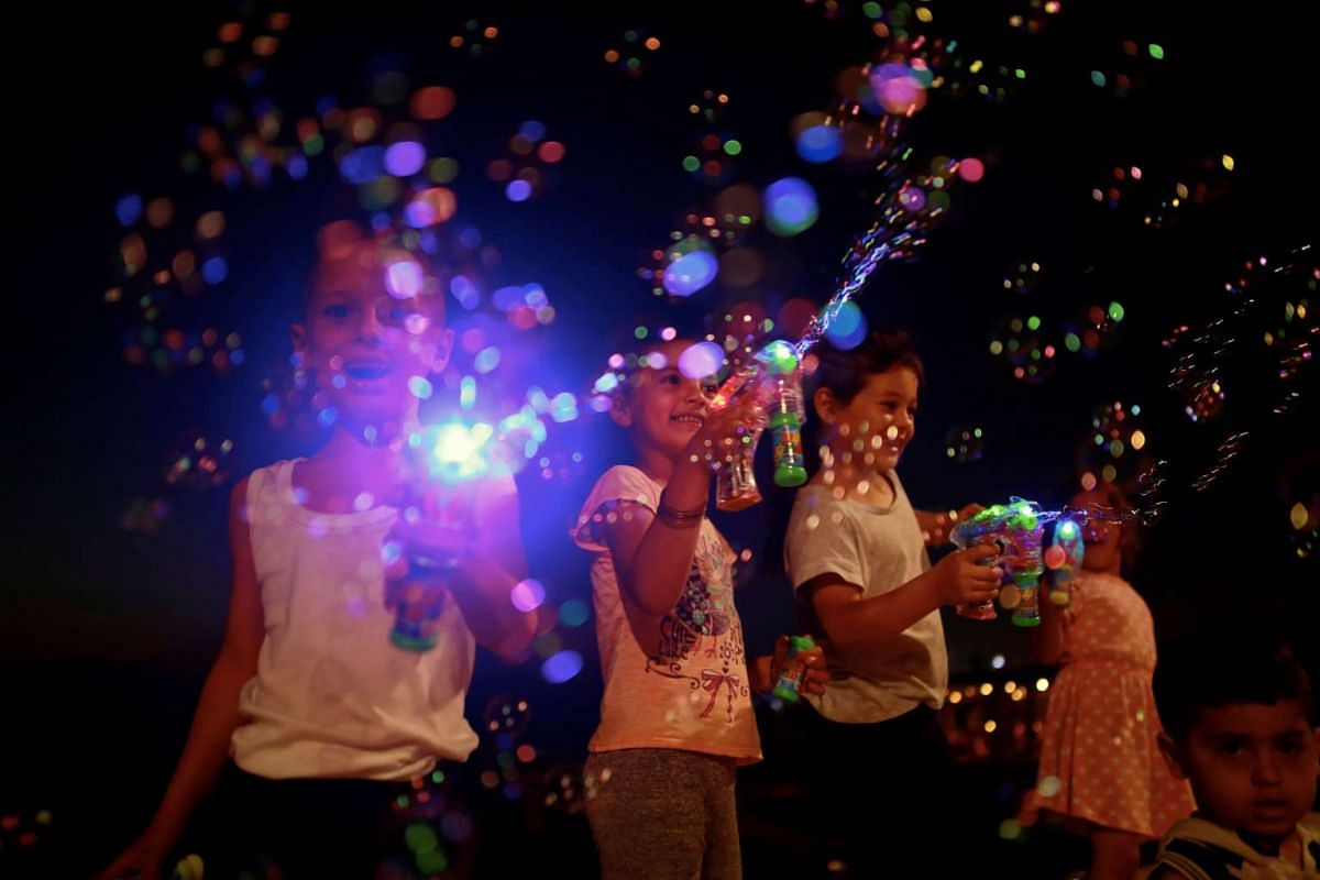 Children play with bubble toy guns along the shore of the Mediterranean Sea during the Muslim holiday of Eid al-Fitr, in Tel Aviv, Israel June 27, 2017. PHOTO: REUTERS