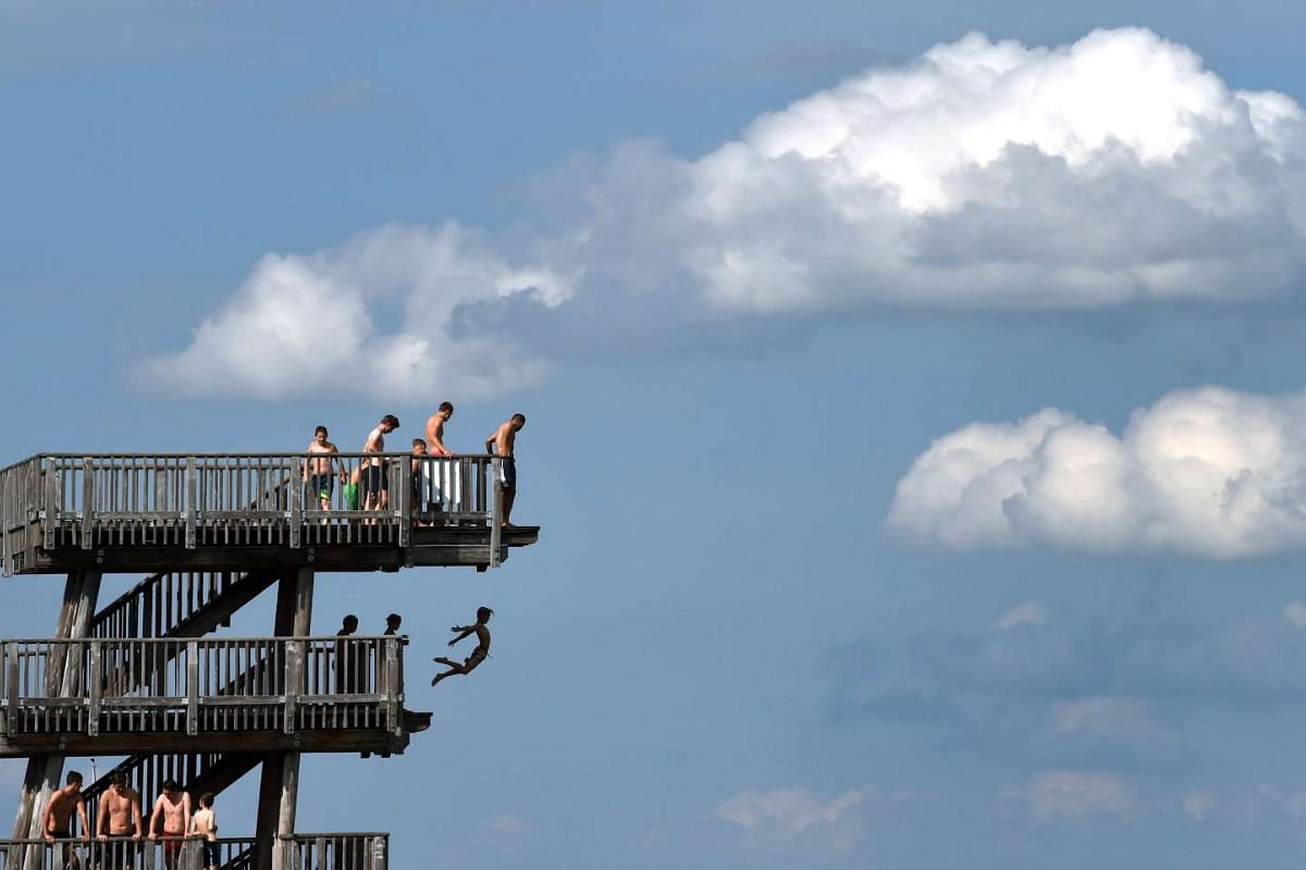 A boy jumps from a diving tower on the shore of the lake Ammersee near the small Bavarian village Utting, southern Germany, on June 27, 2017. PHOTO: AFP