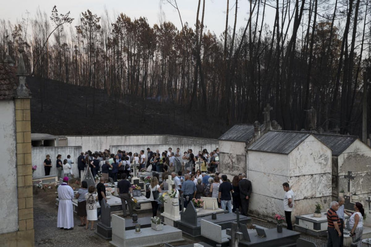 Scorched trees loom over a funeral ceremony held for six victims of the wildfires in the tiny village of Sarzedas de Sao Pedro, on Tuesday (June 20) last week. Portuguese Prime Minister Antonio Costa has asked for explanations about what went wrong i