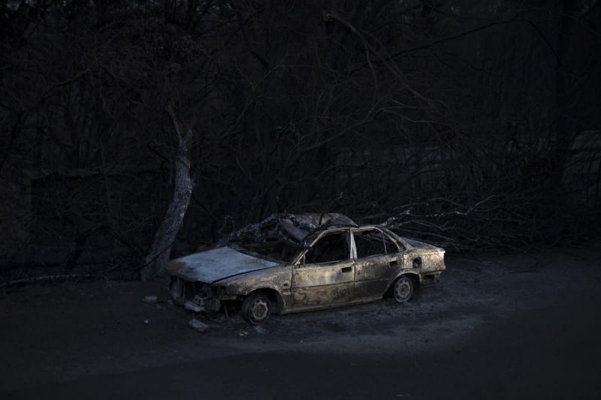 A car that was destroyed in the fires near the village of Souto Fundeiro, Portugal. Residents are criticising the authorities for failing to close the narrow, winding roads where most of those who died had been trapped in their cars.