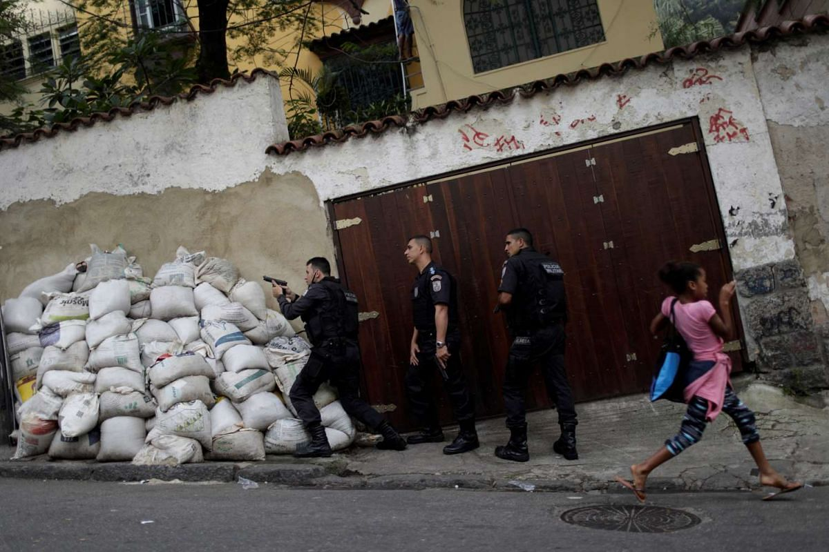 A girl reacts as police officers take up positions after a resident was shot dead during a violent clash during an operation against drug dealers in Pavao Pavaozinho slum in Rio de Janeiro, Brazil, June 28, 2017. PHOTO: REUTERS