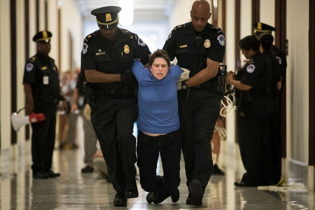 A protestor is arrested by Capitol Police officers outside the office of Sen. Pat Toomey's (R-PA) while lobbying against the Senate GOP health care bill, on Capitol Hill, June 28, 2017 in Washington, DC. PHOTO: GETTY IMAGES/ AFP
