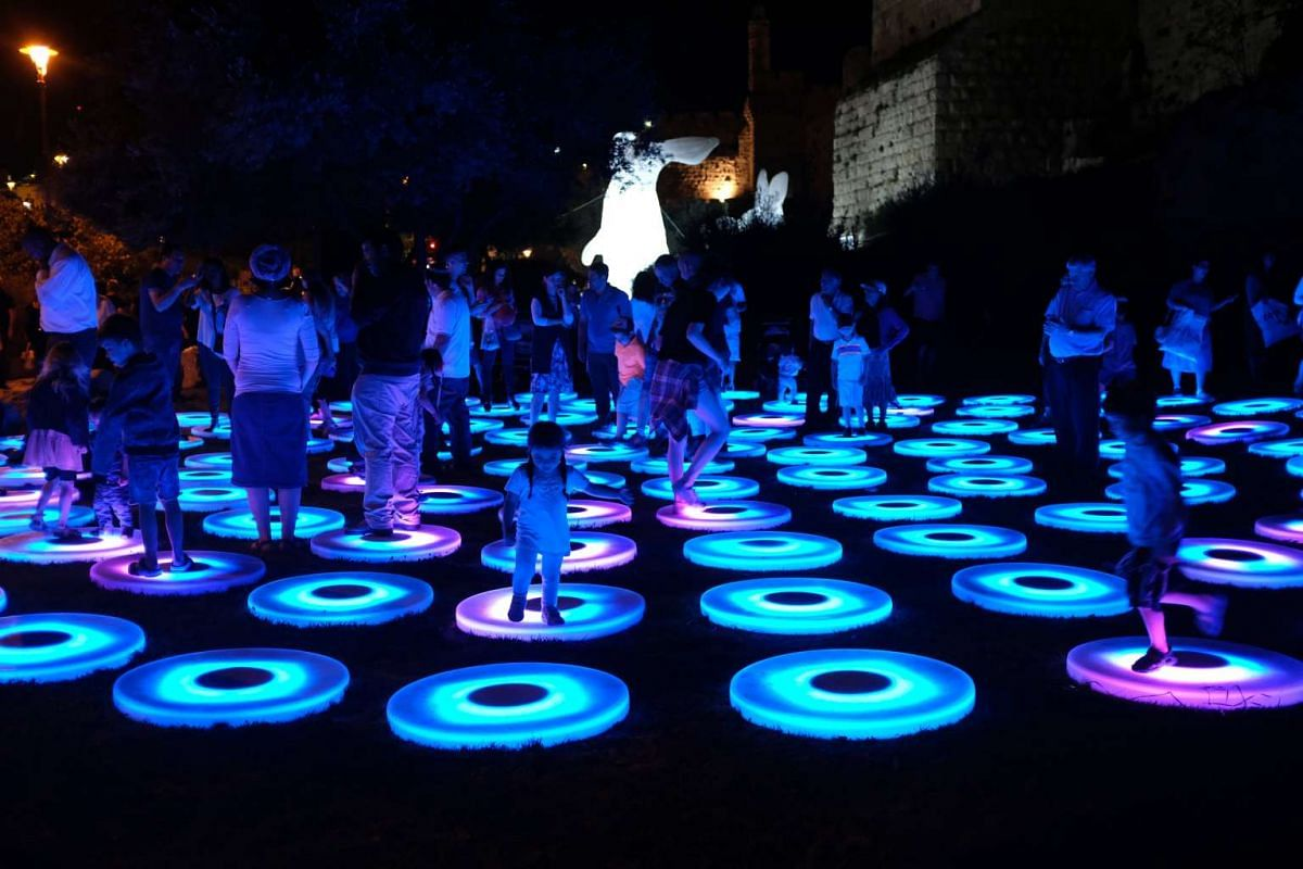 People play on a light installation next to the Old City Walls during the Jerusalem Lights Festival, in the Old City of Jerusalem, Israel, June 28, 2017. PHOTO: EPA