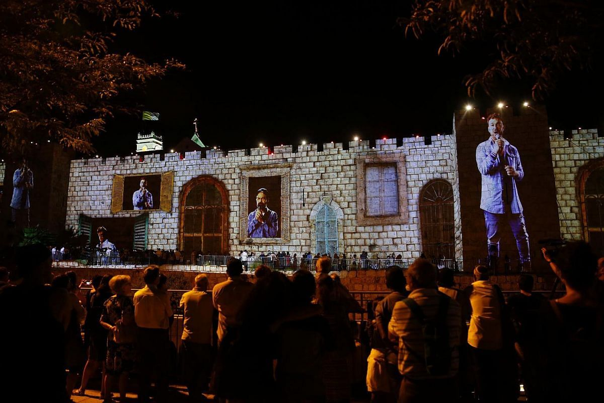 People look at images illuminating the walls of the Old City of Jerusalem as they attend the Light Festival on June 28, 2017.