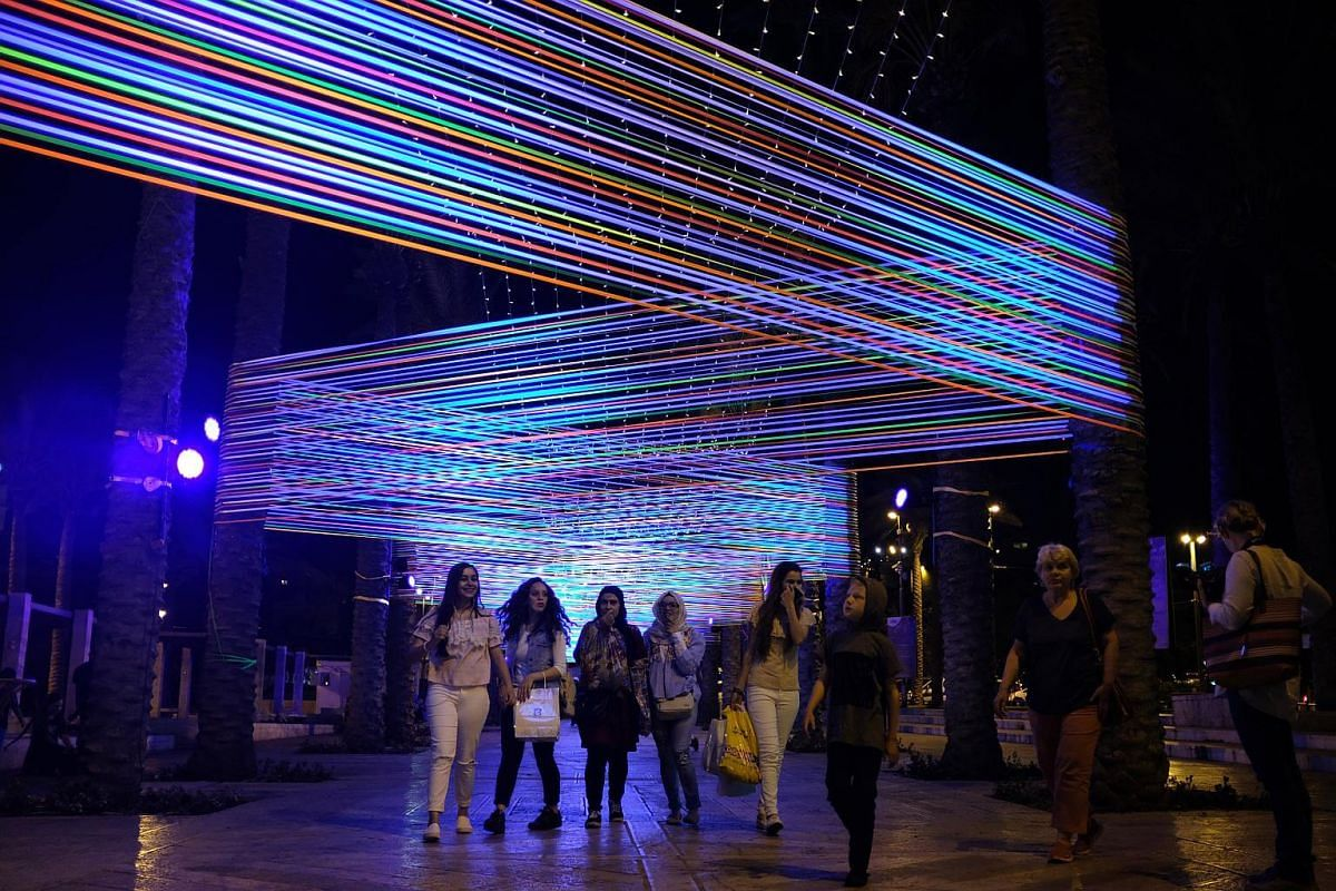 People view a light installation next to the Old City Walls during the Jerusalem Lights Festival, in the Old City of Jerusalem, on June 28, 2017.