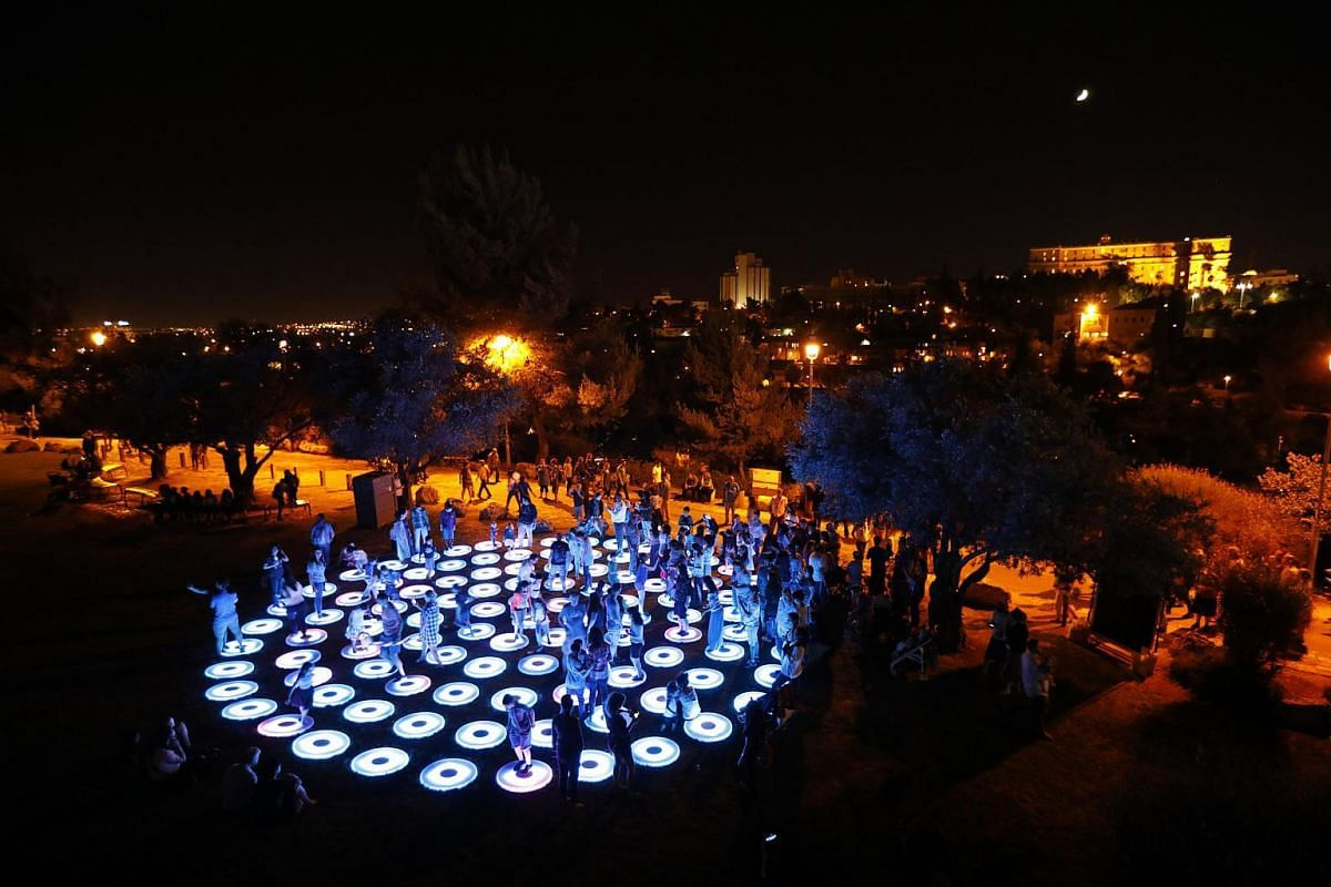 People play on a light installation next to the Old City Walls during the Jerusalem Lights Festival, in the Old City of Jerusalem, on June 28, 2017.