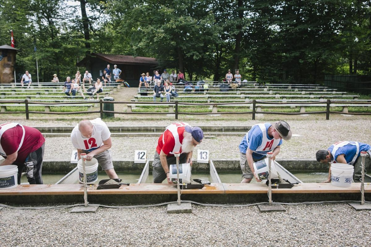 Goldpanners competing in the 36th Italian Gold Panning Championship at the Victimula Gold Panner's Arena in the Bessa Natural Reserve in Zubiena, Italy on June 24, 2017.