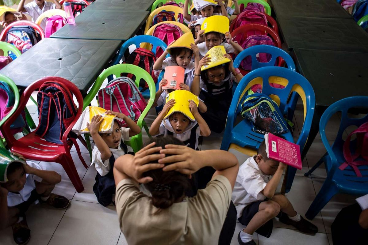 Schoolchildren from the Corazon Aquino Elementary School participate in a nationwide simultaneous earthquake drill in Manila on June 29, 2017. PHOTO: AFP
