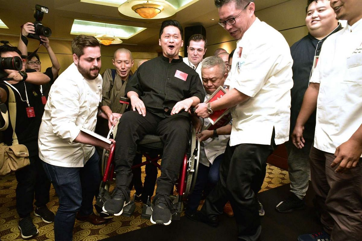 Chef Muhammad Haikal Johari of Alma restaurant is helped onto the stage for a group photo at the Michelin Guide Singapore event on June 29, 2017. PHOTO: THE STRAITS TIMES/DESMOND WEE