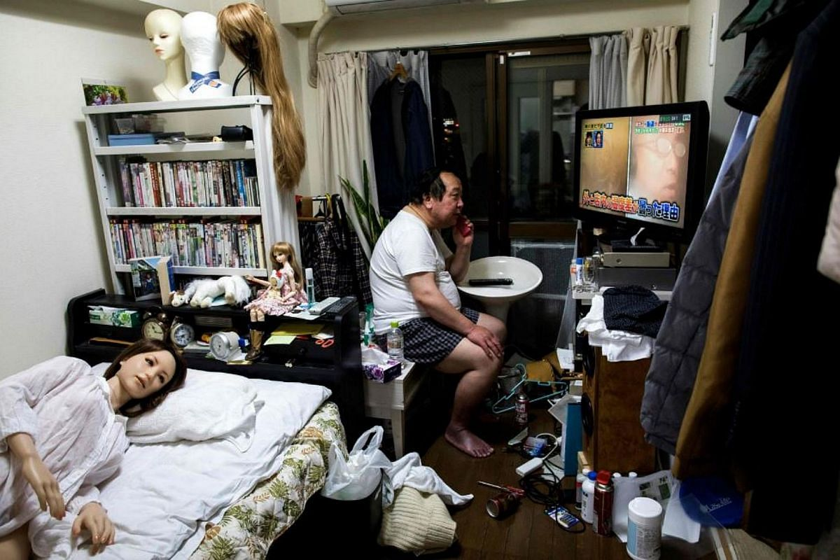 Senji Nakajima, 62, speaks on his mobile phone as his silicone sex doll Saori (left) lies in bed at his apartment on the outskirts of Tokyo.