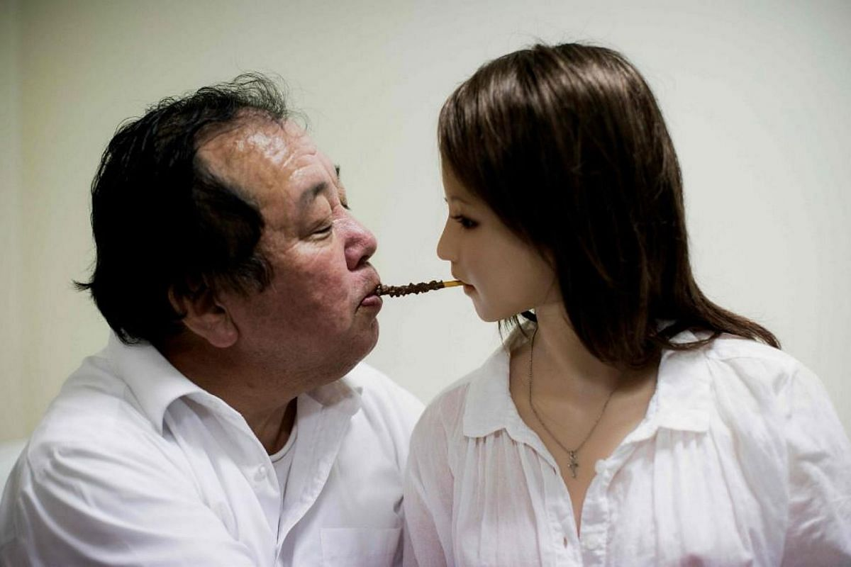 Senji Nakajima, 62, (left) shares a chocolate stick with his silicone sex doll Saori in bed at his apartment on the outskirts of Tokyo.