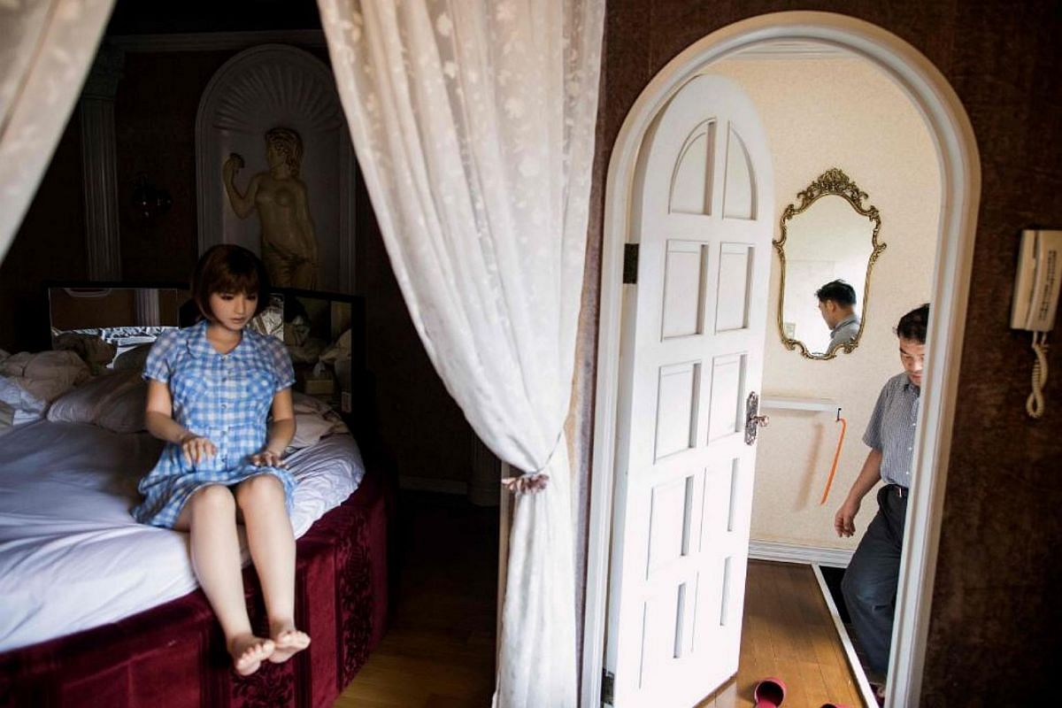 Physiotherapist Masayuki Ozaki (right) prepares to check out of a love hotel after spending a night with his silicone sex doll Mayu in Yachimata, Chiba prefecture.