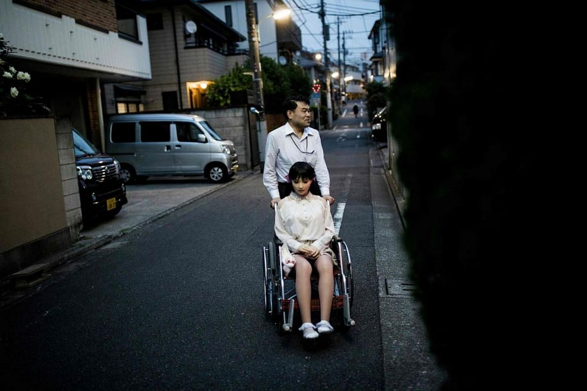 Physiotherapist Masayuki Ozaki stands with his silicone sex doll Mayu outside his apartment in Tokyo.