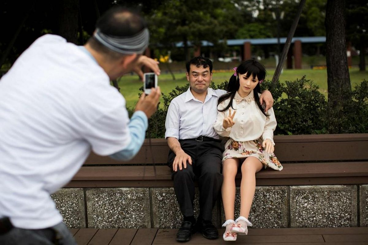 A man takes pictures of physiotherapist Masayuki Ozaki and his silicone sex doll Mayu in Tokyo Bay.