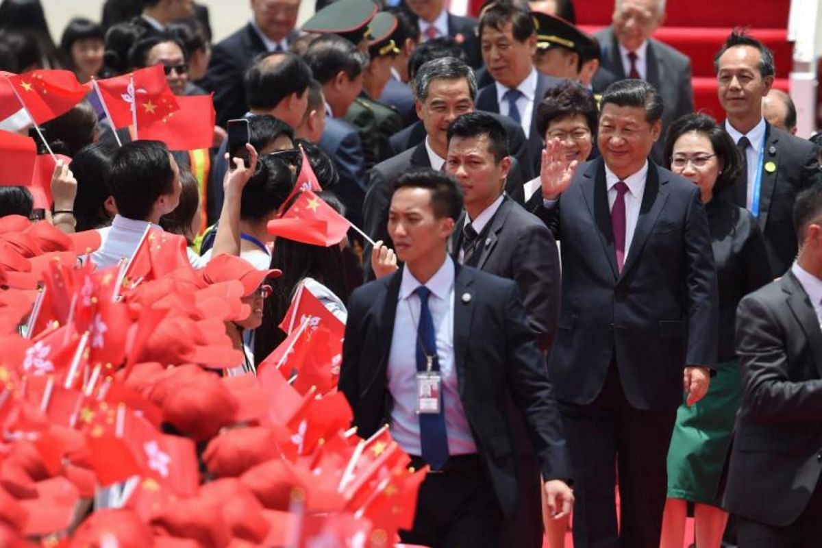 China's President Xi Jinping (right) waving to well-wishers upon his arrival at Hong Kong's international airport, on June 29, 2017.