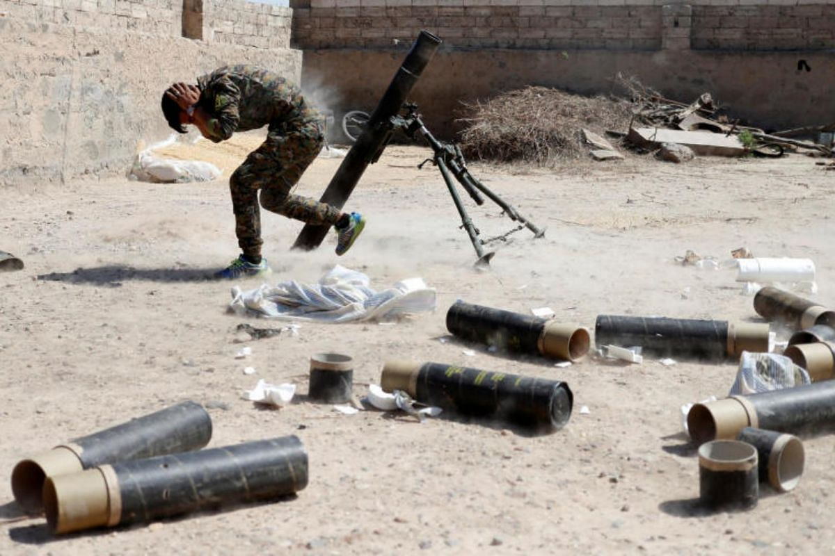 A Kurdish fighter from the People's Protection Units (YPG) firing a 120 mm mortar round in Raqqa, Syria, on June 15, 2017.