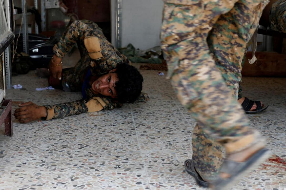A Syrian Democratic Forces fighter injured by sniper fired by ISIS militants lies on the ground in a field hospital in Raqqa, on June 28, 2017.
