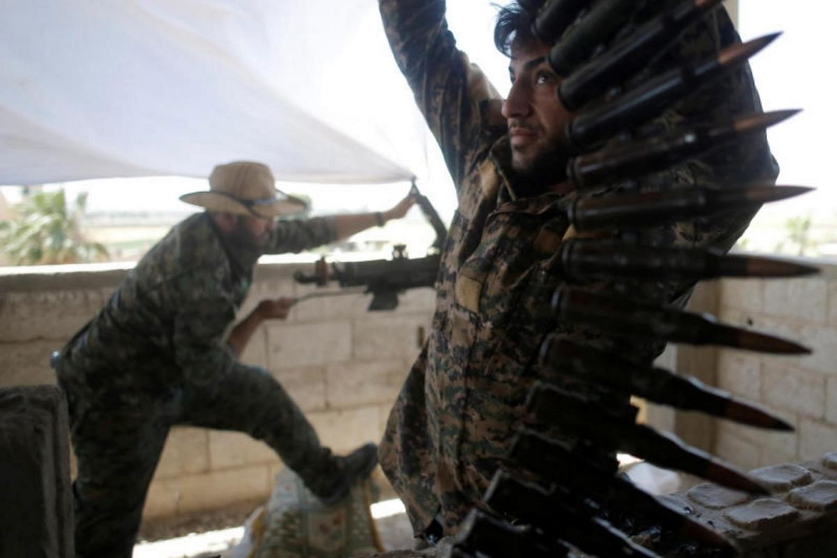 A Kurdish fighter from the People's Protection Units carries ammunition in Raqqa, on June 21, 2017.