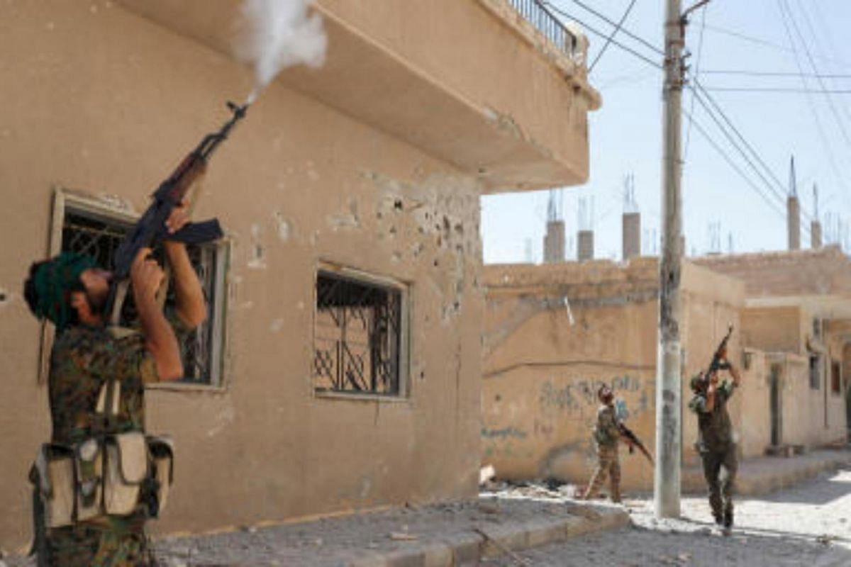 Kurdish fighters from the People's Protection Units firing rifles at a drone operated by ISIS militants in Raqqa, on June 16, 2017.