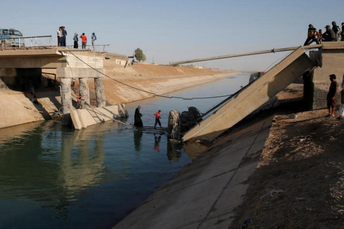 People crossing a makeshift ladder in a village near Raqqa after a bridge was destroyed in fighting between the US-led coalition and ISIS, Raqqa, on June 16, 2017.
