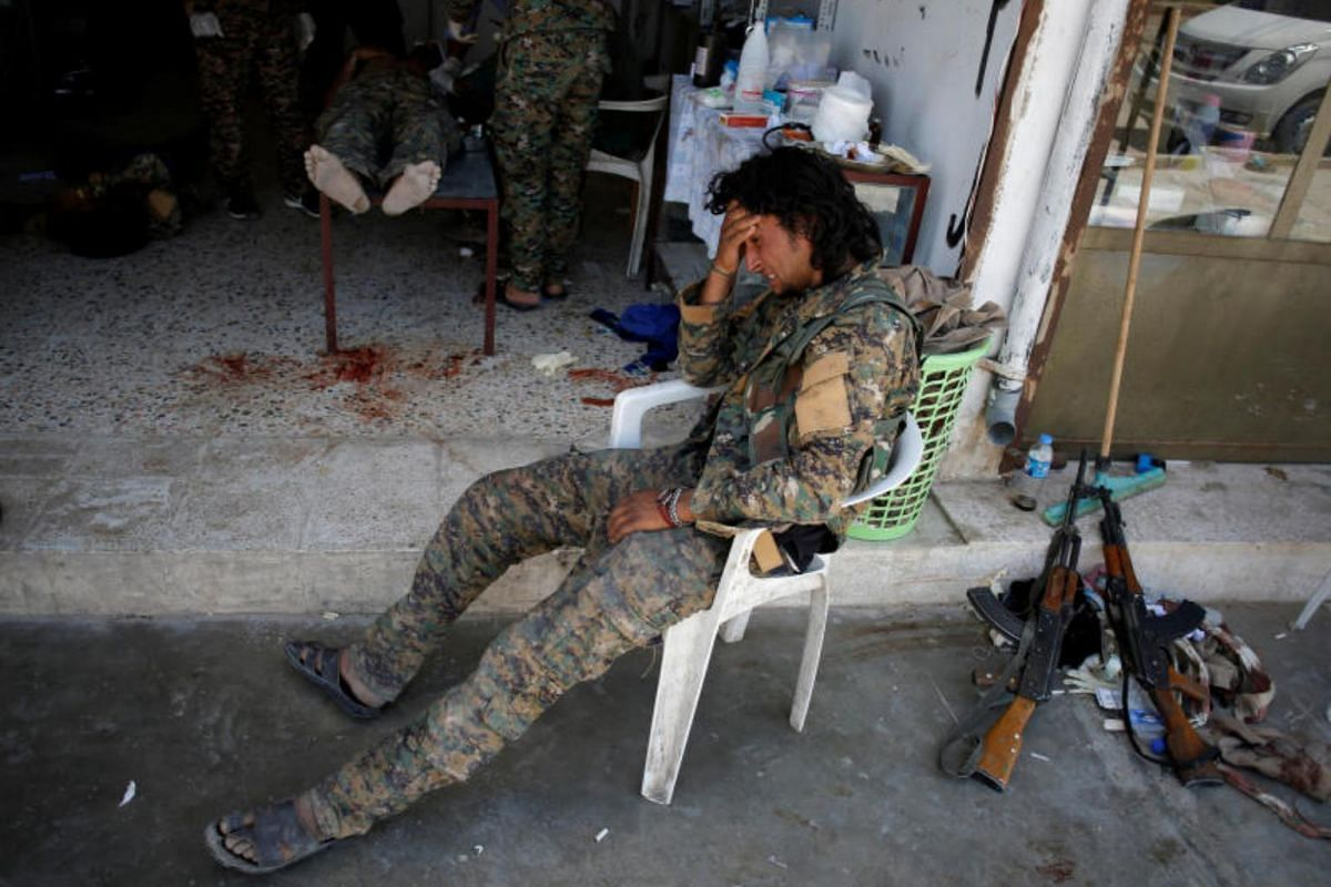 A Syrian Democratic Forces fighter (SDF) cries as medics treat his comrades injured by sniper fired by  ISIS militants in a field hospital in Raqqa, on June 28, 2017.