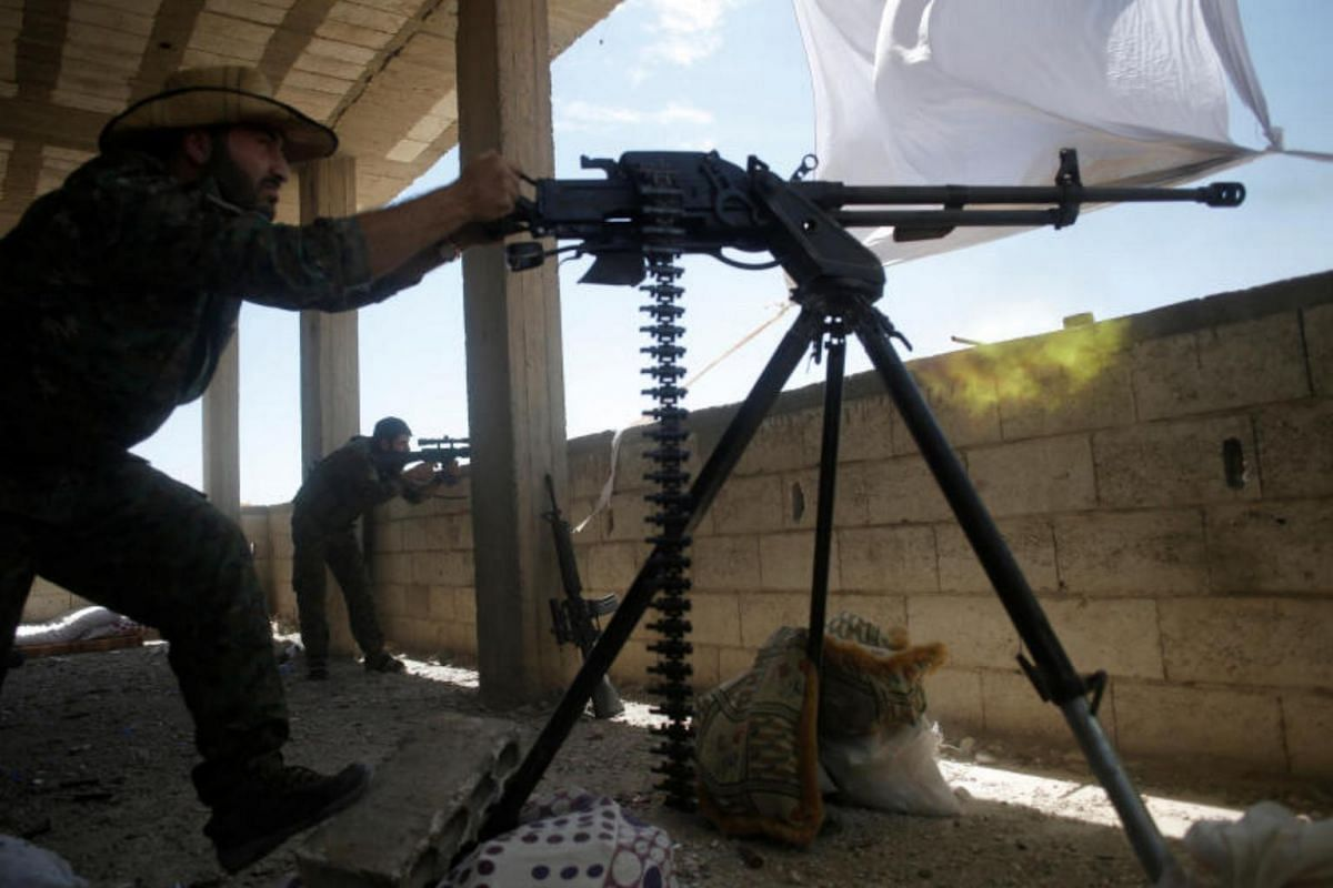 A Kurdish fighter from the People's Protection Units firing heavy machine-gun at Islamic State militants in Raqqa, on June 21, 2017.