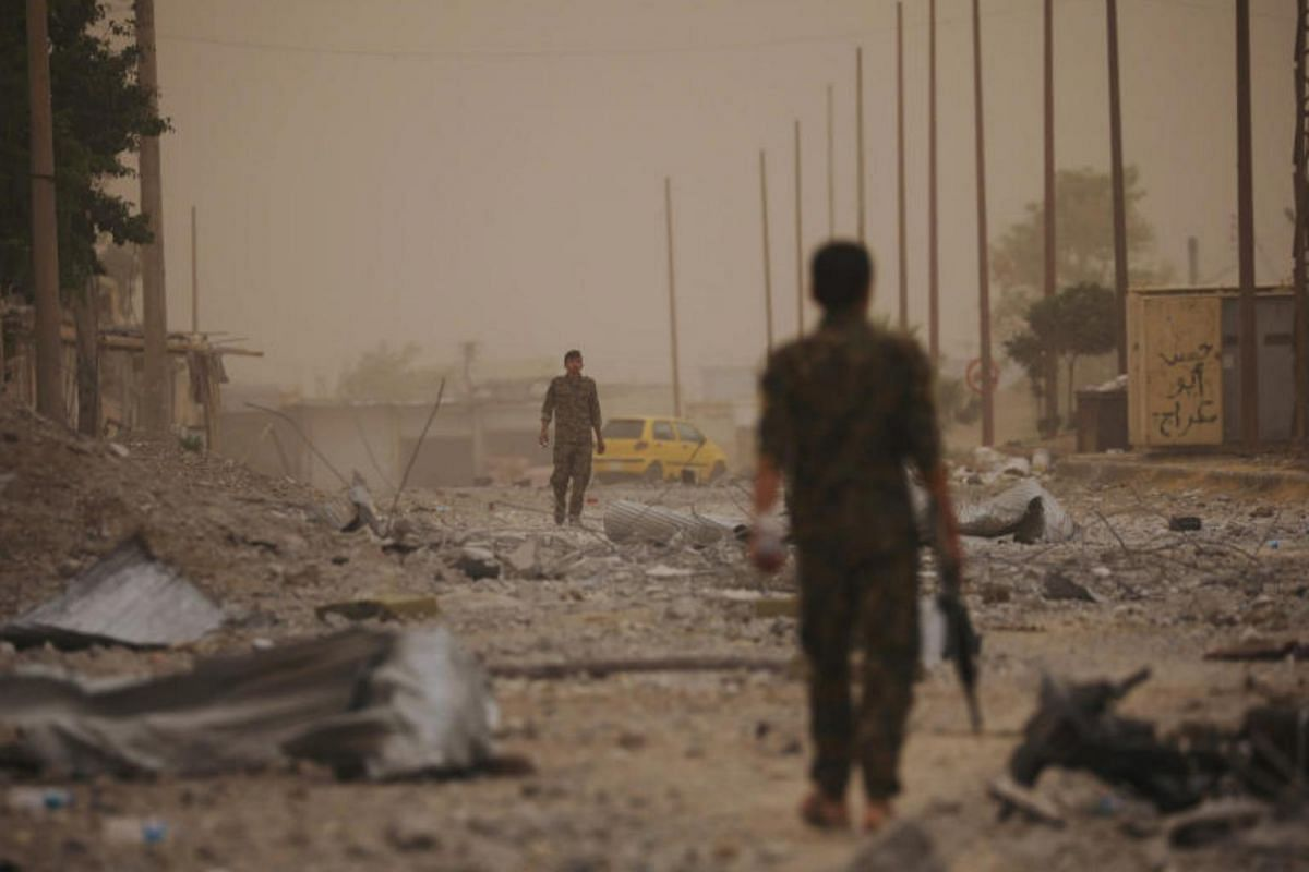 Syrian Democratic Forces fighters walking on the rubble of a damaged street in the Raqqa's al-Sanaa industrial neighbourhood, on June 14, 2017.