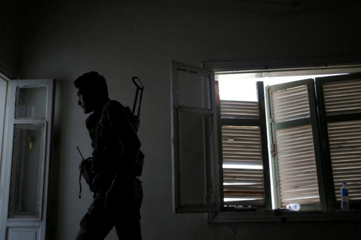 A Syrian Democratic Forces fighter walking in a house in Raqqa, on June 27, 2017.
