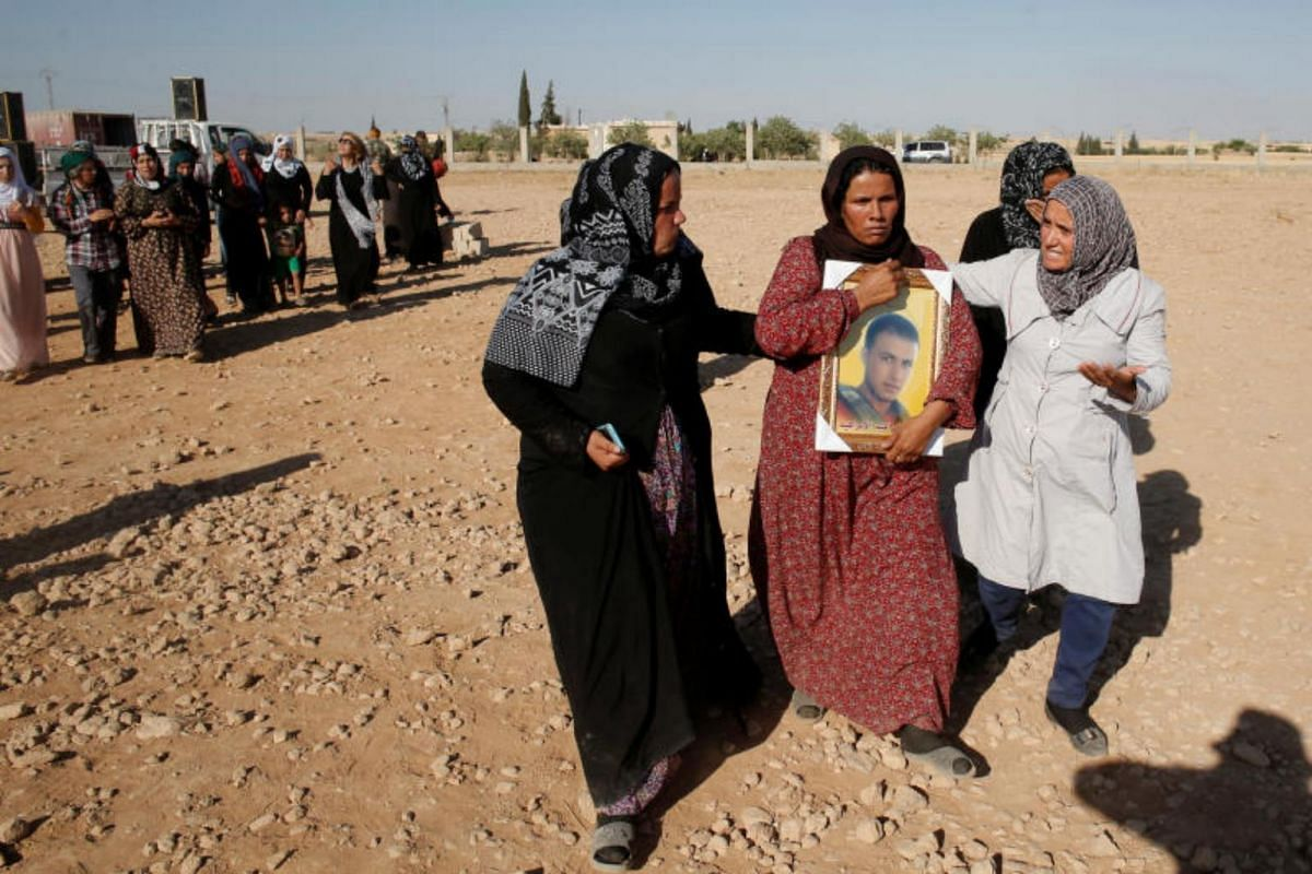 A woman holding a picture of her son, a Syrian Democratic Forces fighter who was killed by ISIS militants in Raqqa, during a funeral in Tal Abiad, on June 23, 2017.
