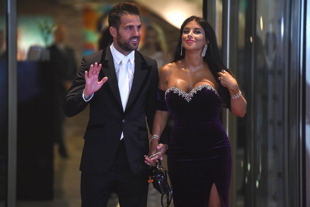 Chelsea's football player Cesc Fabregas and his wife posing on a red carpet upon arrival to attend Argentine football star Lionel Messi and Antonella Roccuzzo's wedding in Rosario, Santa Fe province, Argentina on June 30, 2017.