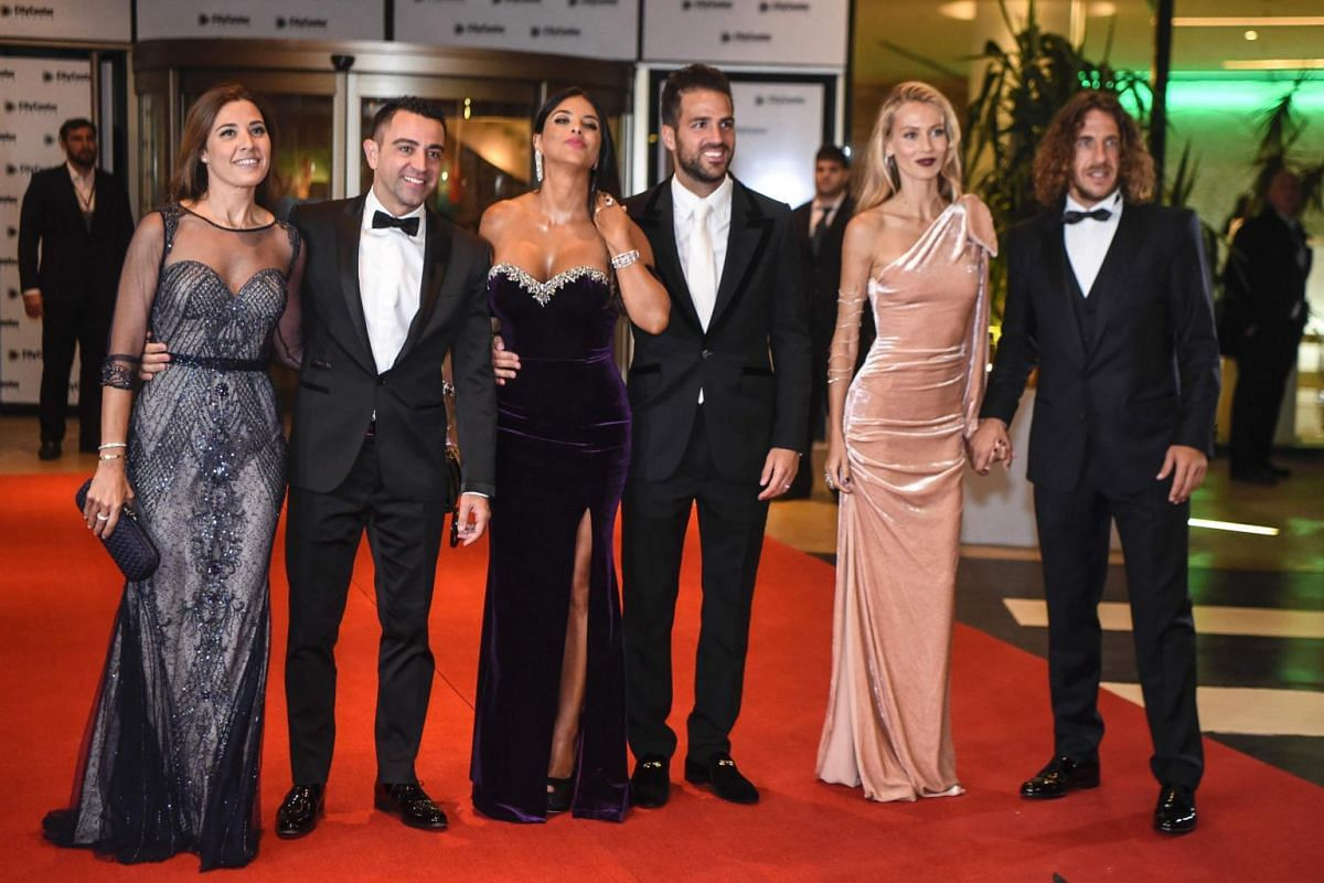 Former Barcelona players (from left) Xavi Alonso, Cesc Fabregas and Carles Puyol and their wives posing on a red carpet upon arriving at the wedding in Rosario, Santa Fe province, Argentina on June 30, 2017.