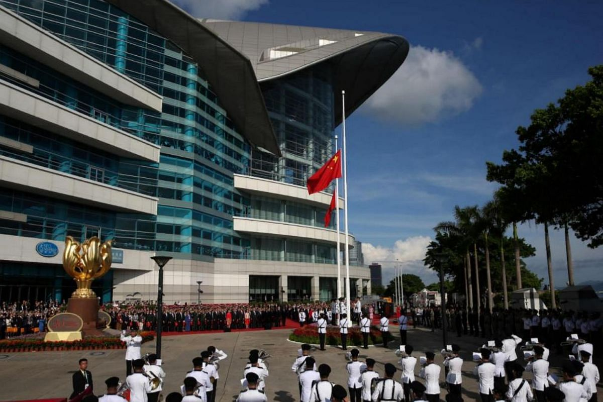 The Chinese (front) and Hong Kong (behind) flags are raised during a ceremony at Golden Bauhinia Square in Hong Kong, on July 1, 2017.
