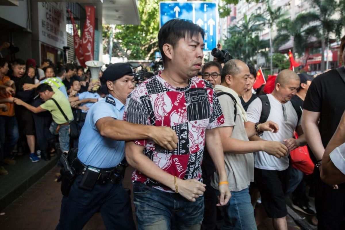 A policeman tries to detain a pro-Chinese activist (centre) during a pro-democracy protest in Hong Kong, China, on July 1, 2017.