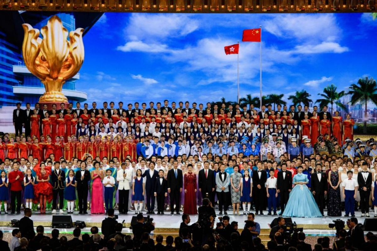 Chinese President Xi Jinping (centre, right wearing red tie) sings a song entitled My Country with performers of a variety show along with outgoing chief executive Leung Chun-ying (centre, left) and incoming leader Carrie Lam (centre, right) during h
