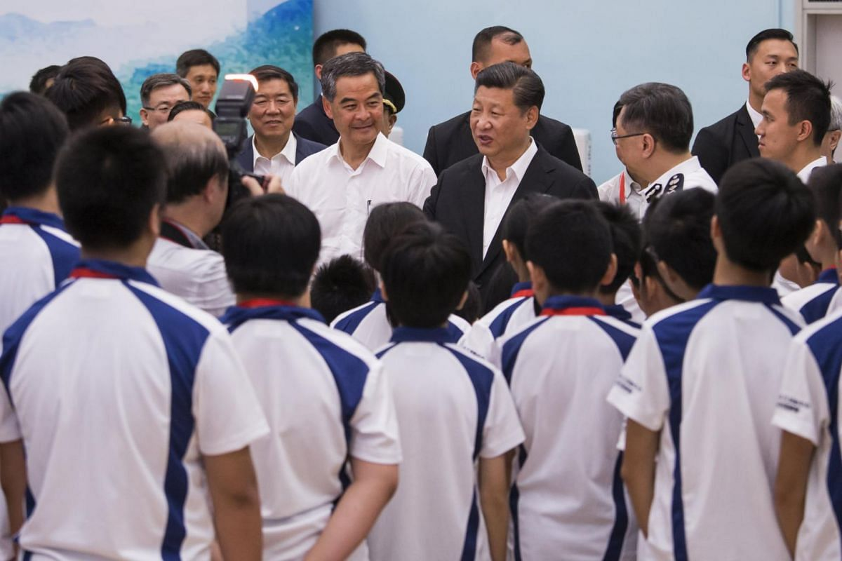 President of China Xi Jinping (centre, right) speaks with members of the Hong Kong Police Force's Junior Police Scheme as Leung Chun-ying (centre, left), Hong Kong's outgoing chief executive, looks on during a visit at the scheme's Permanent Activity