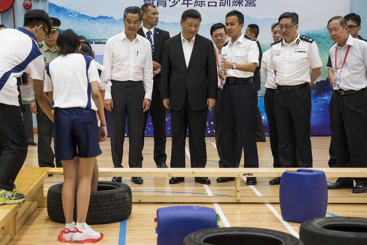 President of China Xi Jinping (centre) and Leung Chun-ying (fourth, left) Hong Kong's outgoing chief executive, look at a demonstration by members of the Junior Police scheme at the scheme's permanent activity centre and integrated youth camp in Hong