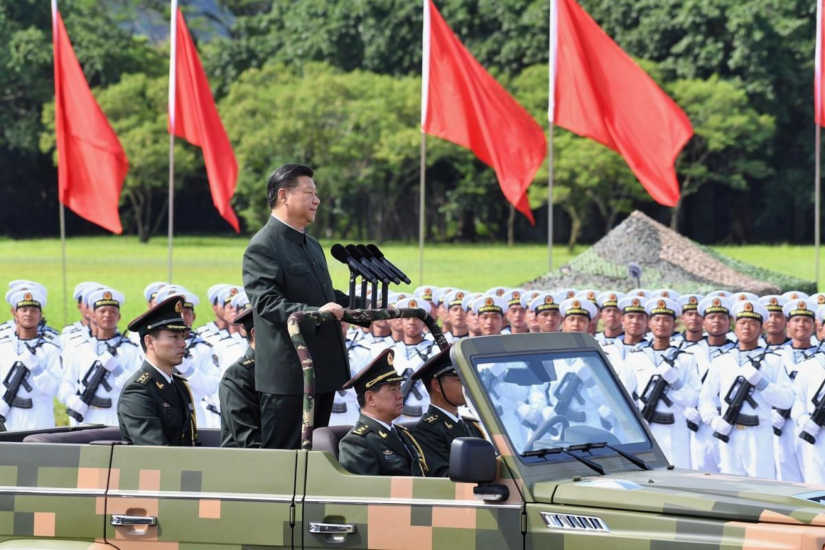 A handout photo made available by Hong Kong's Government Information Services shows Chinese President Xi Jinping (centre) inspecting the troops of the People's Liberation Army Hong Kong Garrison at Shek Kong Barracks in Hong Kong, on June 30, 2017.
