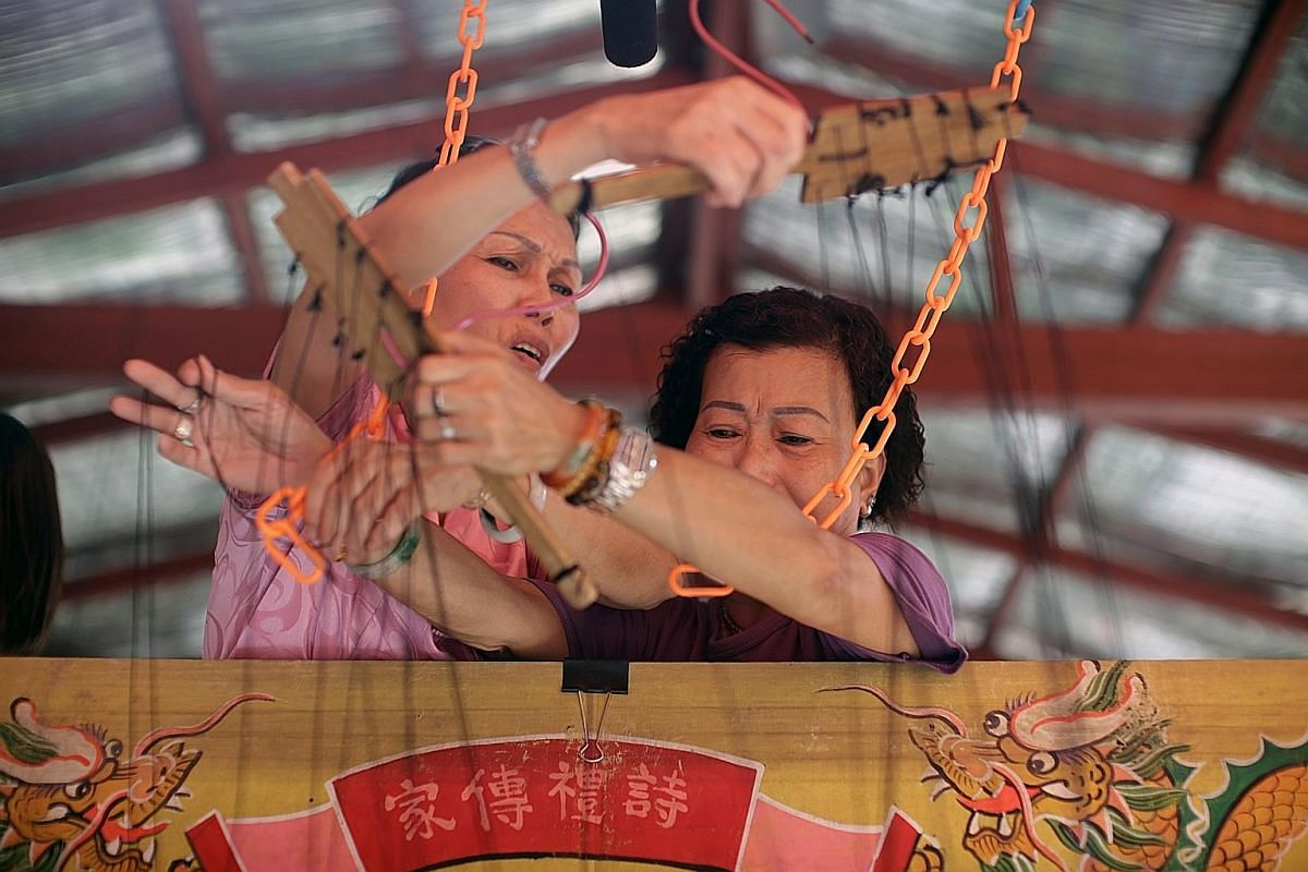Madam Doreen Tan (left) and Madam Tan Poh Hong getting their arms crossed as they skilfully control the many strings that hold up the puppets during an emotionally charged scene. Madam Tan Poh Hong said she got interested in Chinese opera and puppetr