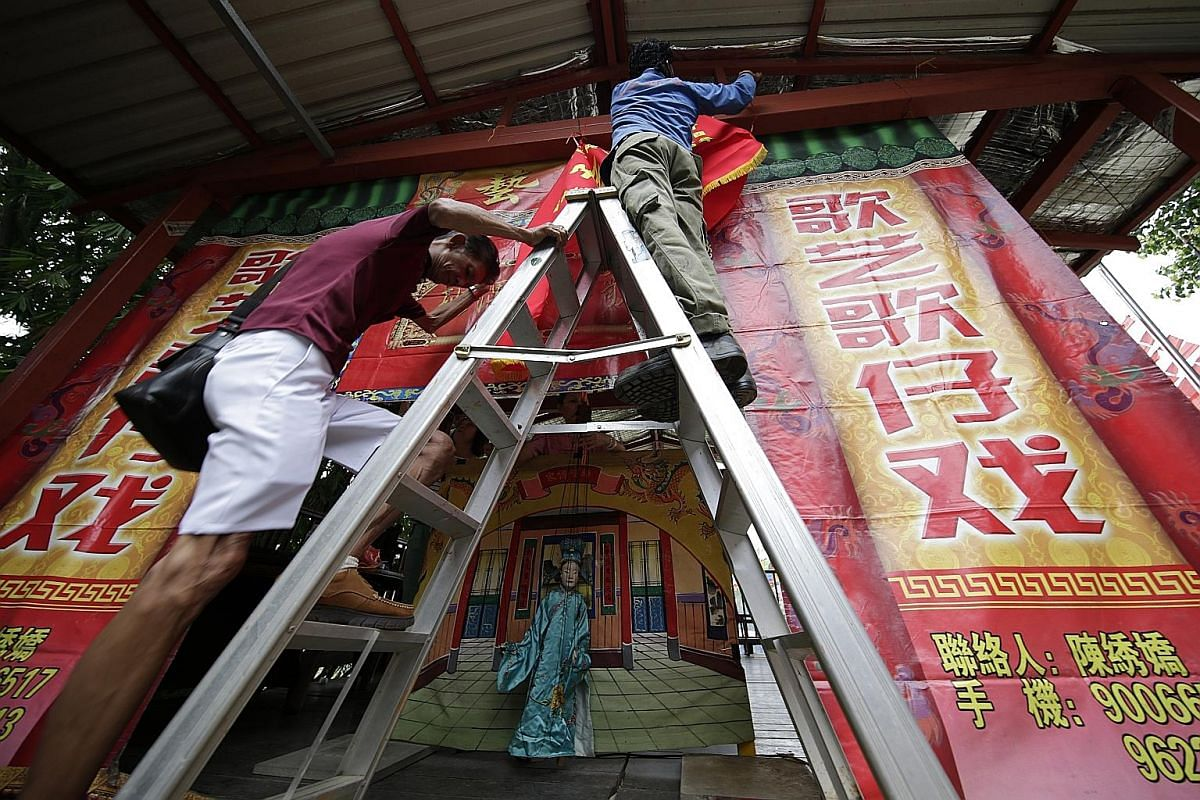Workers putting up a banner in the middle of the performance. The two vertical banners at the side of the stage spell out the troupe's name, Ge Yi Ge Zai Xi, in Chinese. The troupe performs twice a year at Wei To Temple to celebrate the birth or rein