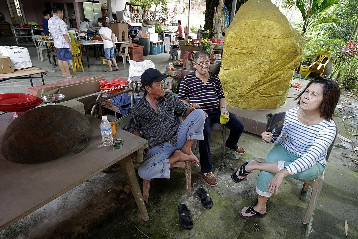 (From left) Musicians Ng Poh Cheng and Chong Ei Hua, both 70, and puppeteer Lim Geok Hwa, 60, take a break before their performance. Behind them is the granite boulder, now painted in gold, that fell on Madam Ong's home 20 years ago - an incident tha