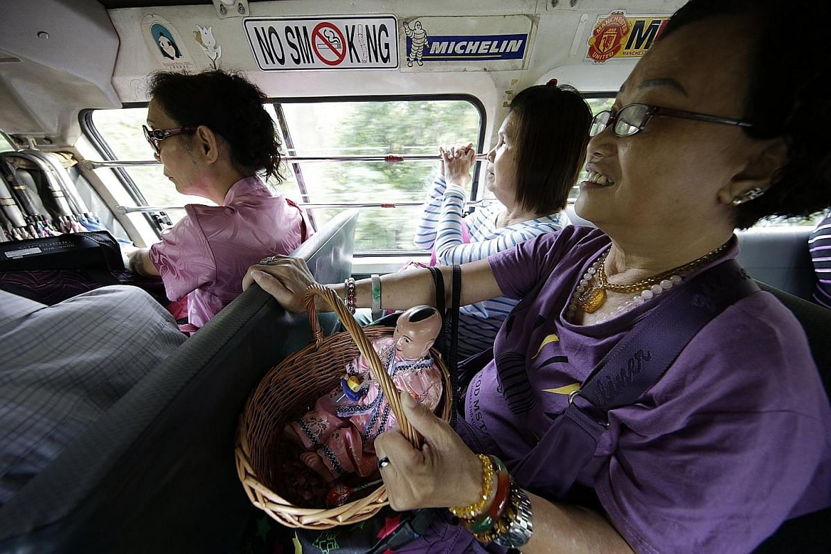 Madam Tan Poh Hong with a figurine of Hai Ji, the Child God of Theatre, on the way to Wei To Temple. Hai Ji, who carries a pacifier, is meant to bless the troupe with a smooth performance.