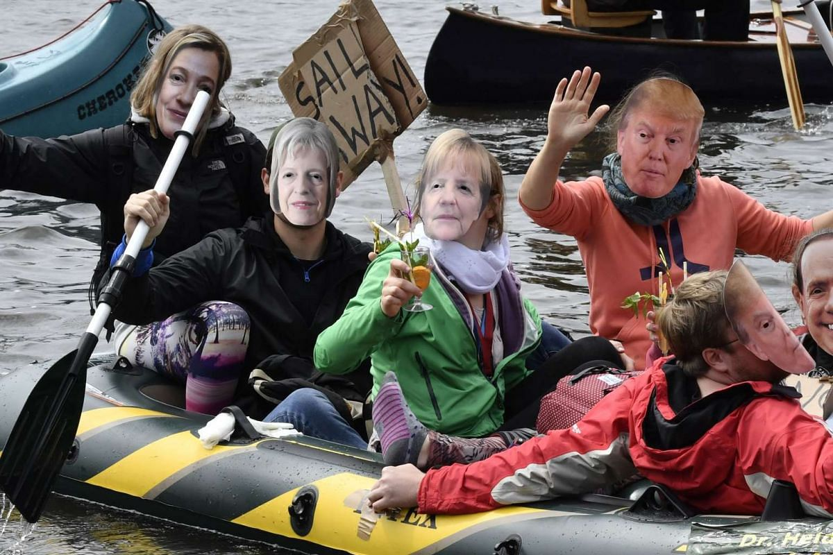 Protestors with masks of politicians (L-R) EU Foreign minister Frederica Mogherini, British Prime minister Theresa Mary, German Chancellor Angela Merkel, US President Donald Trump and Russian Presidet Vladimir Putin drink cocktails in a boat on the A