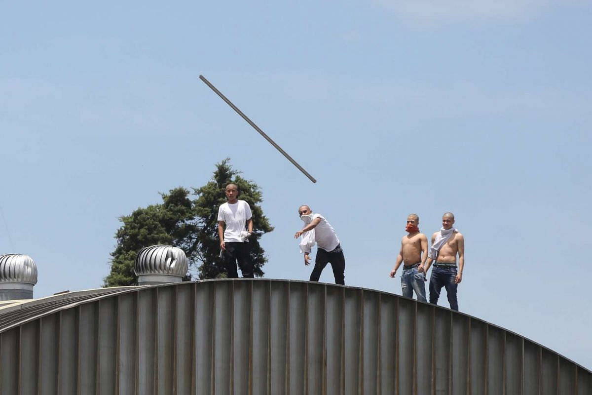 Prisoners occupy the roof of a correctional facility for minors in Guatemala City, Guatemala, July 3, 2017. Authorities were trying to quell a riot at a juvenile detention facility in Guatemala after two teenage inmates apparently committed suicide.T