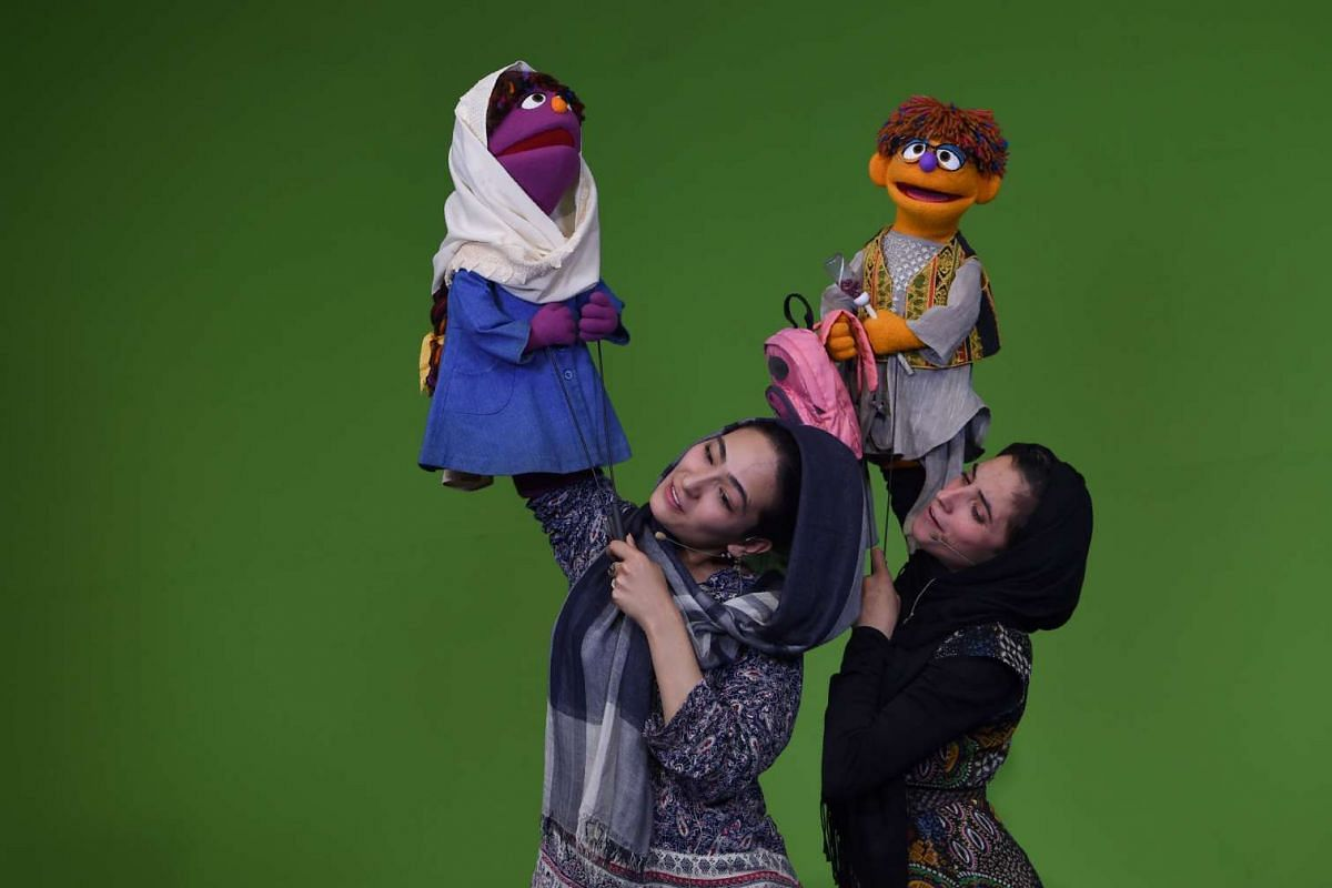 Afghan puppeteers Seema Sultani (R) holds new Sesame Street Muppet 'Zeerak' as she performs with colleague Mansoora Shirzad, holding Muppet 'Zari', during a recording at a television studio in Kabul. The Afghan creators of Zeerak, a bespectacled oran